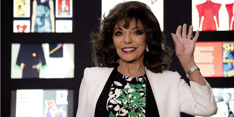 Joan Collins is waving and wearing a dress and white jacket.