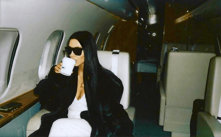 Kim Kardashian wearing sunglasses and a fur coat while sitting on an airplane