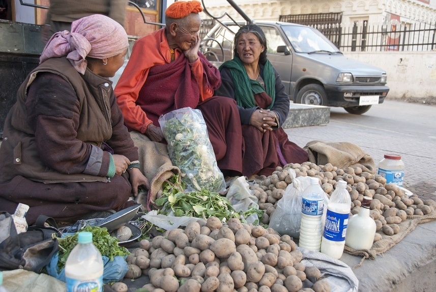 Ladakhi women sell potatoes and milk on sidewalk of street