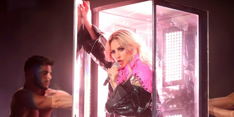 Lady Gaga is getting out of a glass box on stage and is singing.