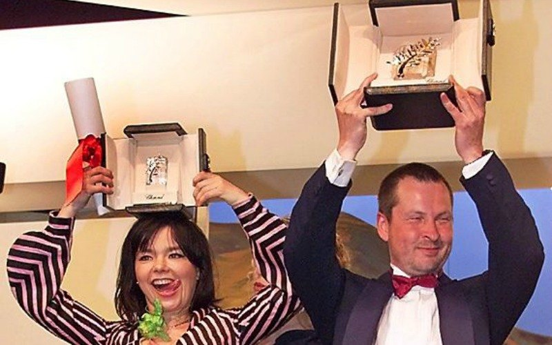 Lars Von Trier and Bjork are holding up Golden Palm 2000 trophies over their heads.
