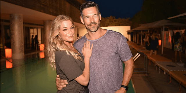 Leanne Rimes and Eddie Cibrian and posing together in front of a hotel.
