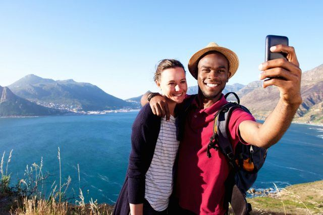 Young couple on holiday taking selfie.