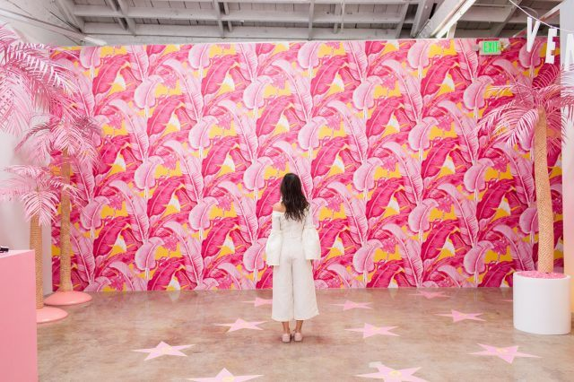 woman standing in front of pink, feather-painted walls