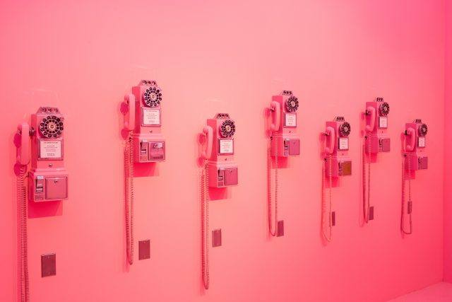 phones on pink wall of museum