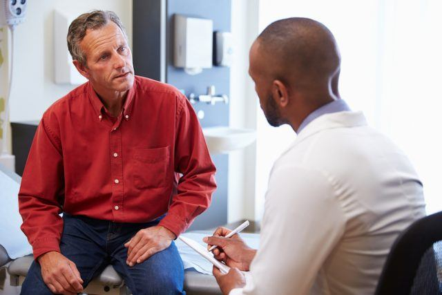 A doctor and his patient talking inside a medical room.