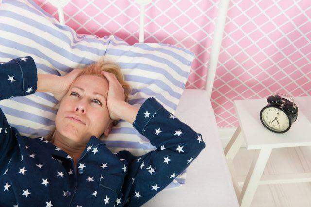 Mature woman with insomnia lying on her bed.