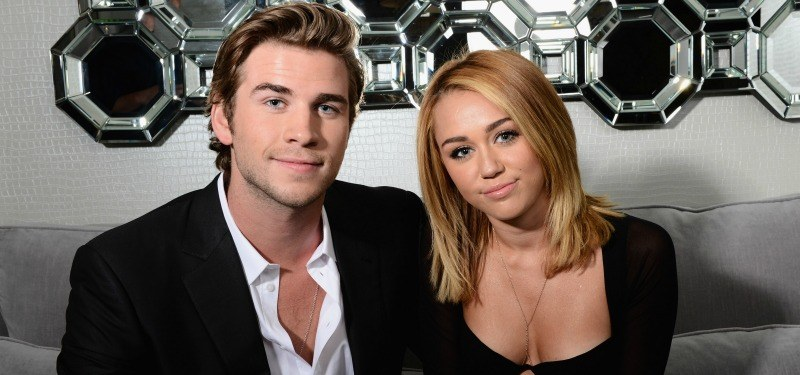 Miley Cyrus and Liam Hemsworth are sitting together and smiling.
