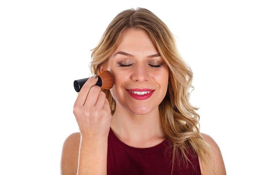 Beautiful woman finishing up her make-up