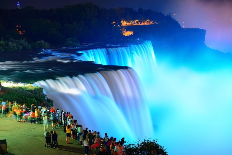 Niagara Falls lit at night by colorful lights