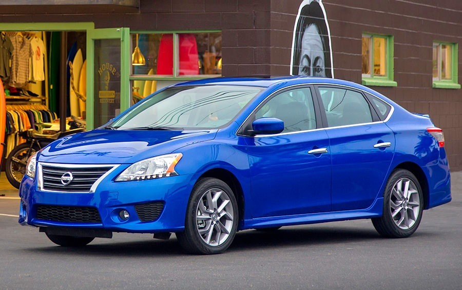 Side view of blue 2014 Nissan Sentra outside surf shop in Venice, California