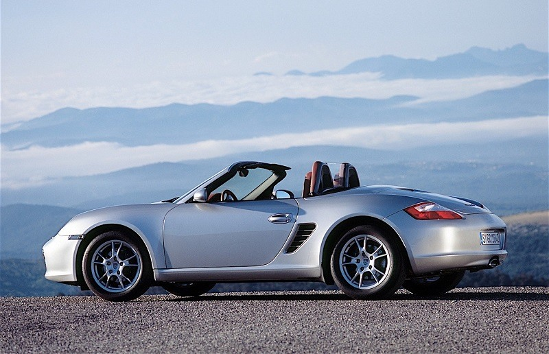 View of a silver 2006 Porsche Boxster roadster with the top down at dusk