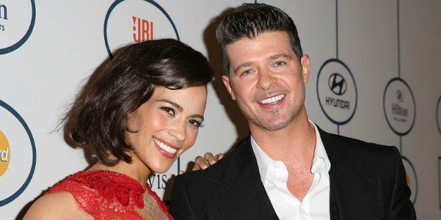 Paula Patton and Robin Thicke are posing together on the red carpet.