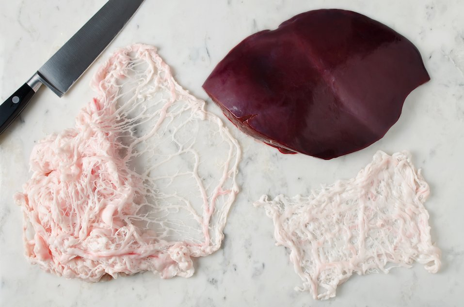 Raw liver and animal fat net on a marble table