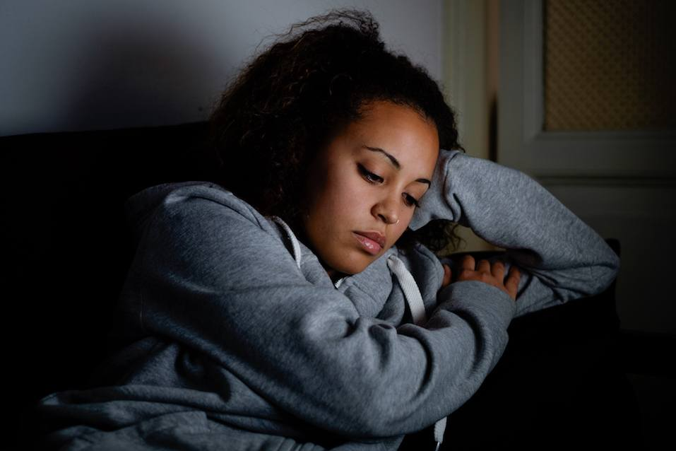 Sad woman lying on the couch at night
