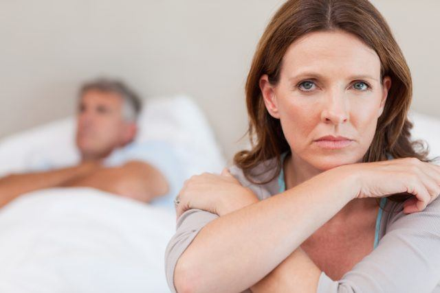 sad woman looking at the camera and sitting at the edge of the bed while her husband looks on