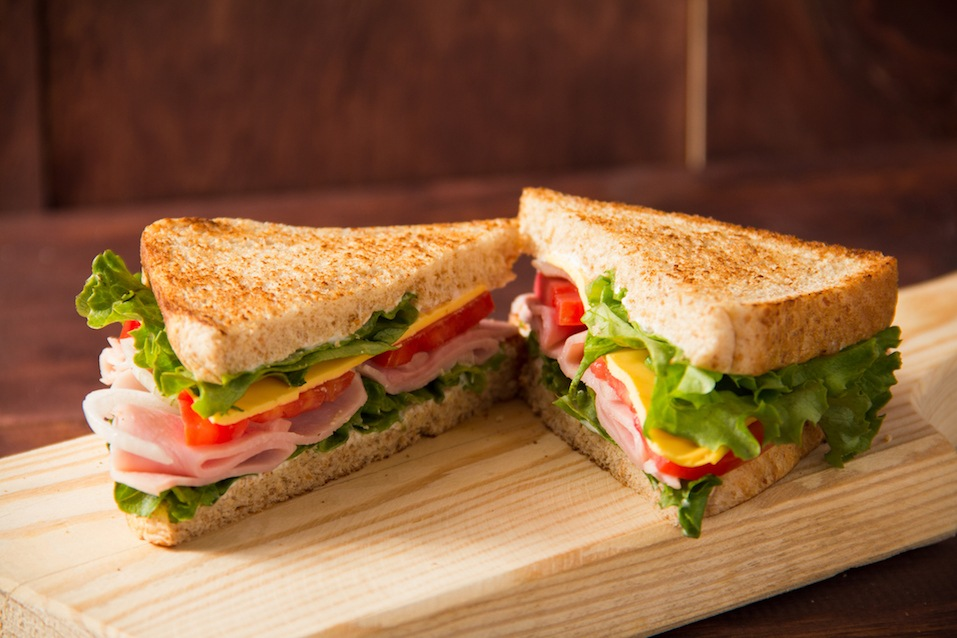 Sandwich tomato, lettuce, onion and yellow cheese on a wooden table