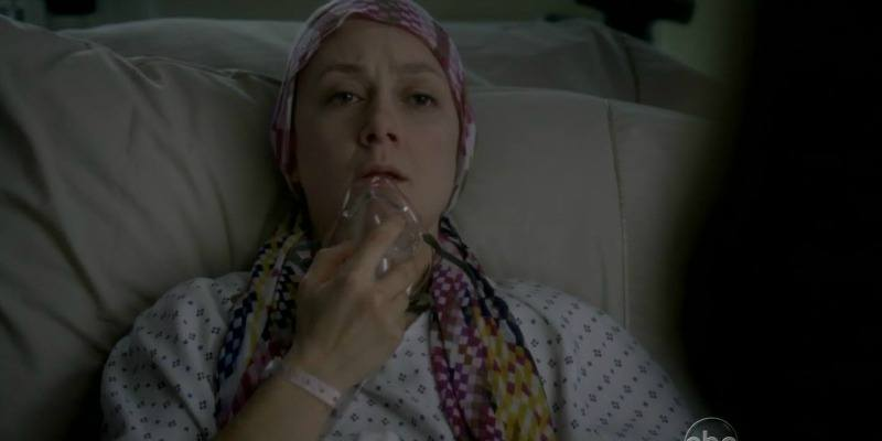 Sara Gilbert has a head scarf on her head and is in a hospital gown. She is pulling an oxygen mask down from her mouth.