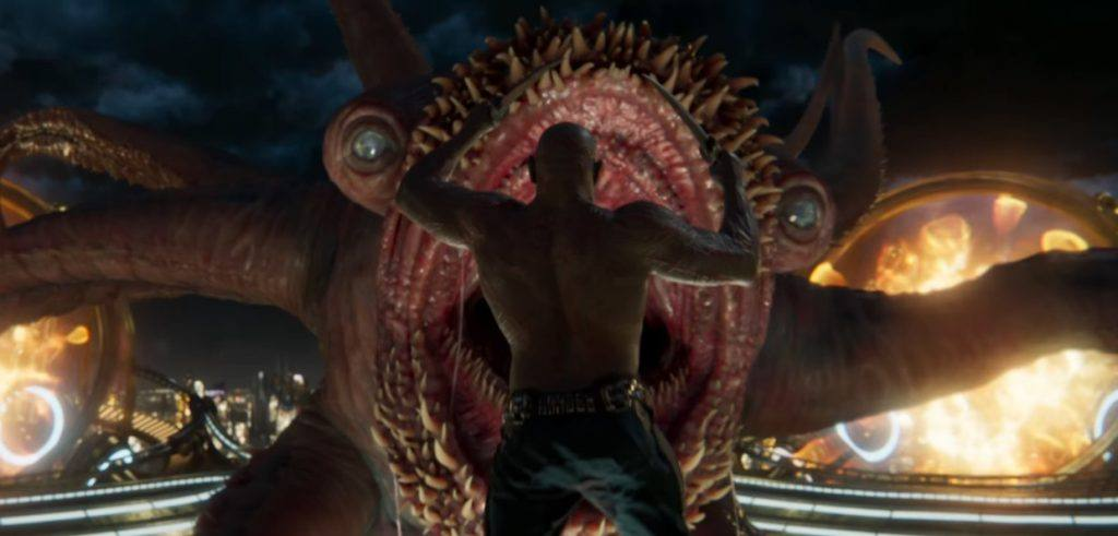 Drax with knives in both hands, jumping directly at a giant monster