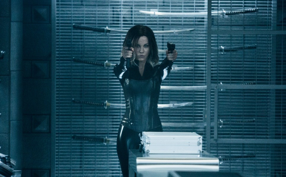 Kate Beckinsale in a black leather suit, holding our twin guns, standing against a rack of swords