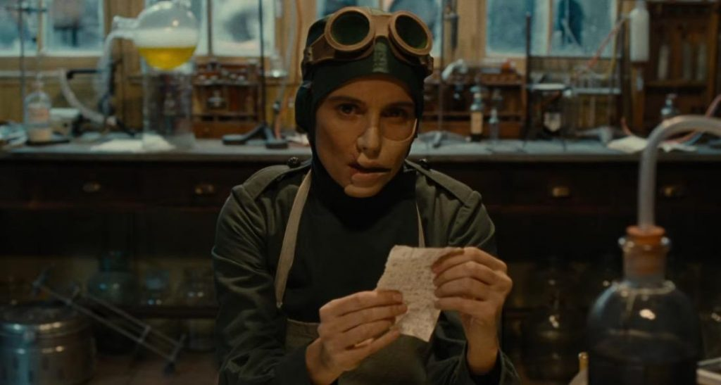Doctor Poison, wearing a medical apron and goggles, holding a piece of paper