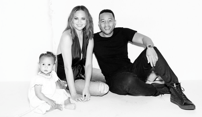 Chrissy Teigen and John Legend pose with their daughter Luna in a black-and-white photo