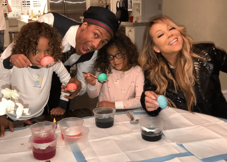 Nick Cannon and Mariah Carey pose with their twins Morrocan and Monroe while dying Easter Eggs