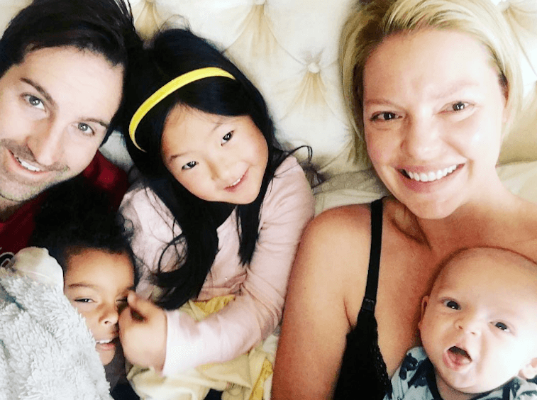 Katherine Heigl in a bed with her husband and three children