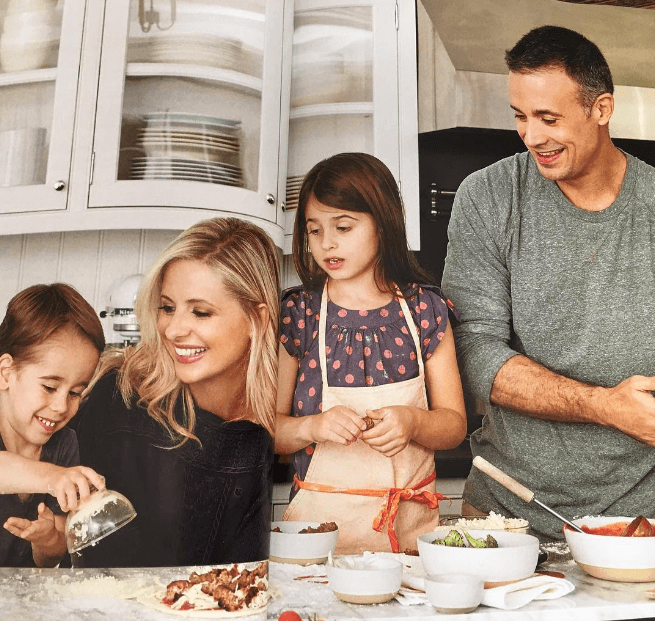 Sarah Michelle Gellar with Freddie Prinze Jr. and their kids making food in the kitchen