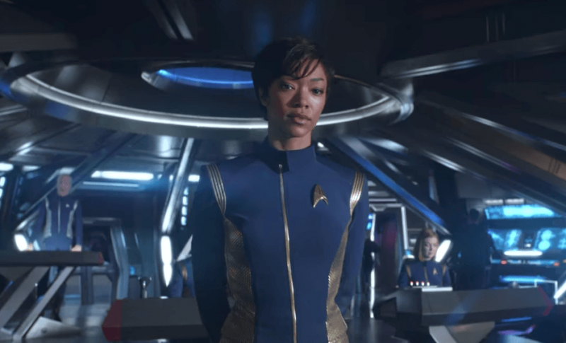 Sonequa Martin-Green stands with her hands behind her back, in a blue Starfleet jumpsuit