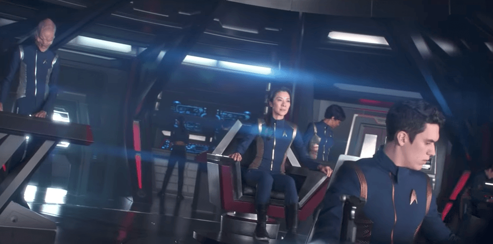 The crew of the Discovery, going about their business on the bridge, all wearing blue jumpsuits