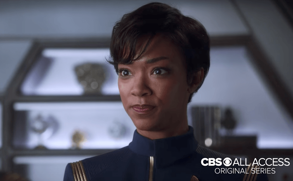 Sonequa Martin-Green, with short hair and a blue, collared jumpsuit.