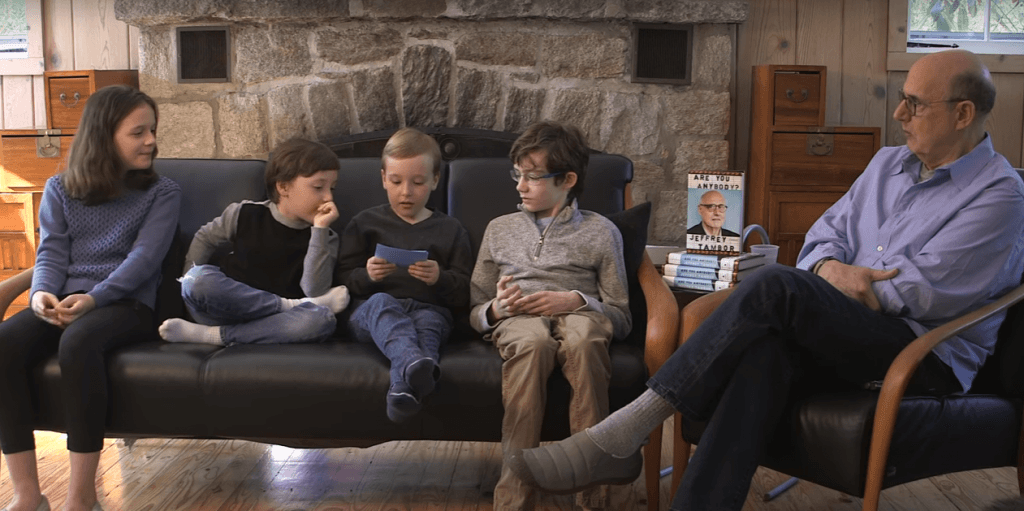 Jeffrey Tambor sits in a chair next to his new book and his four young children