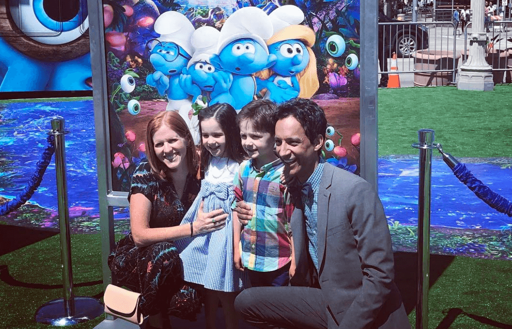 Danny Pudi, his wife, and their twins pose in front of a giant poster for 'Smurfs: The Lost Village'