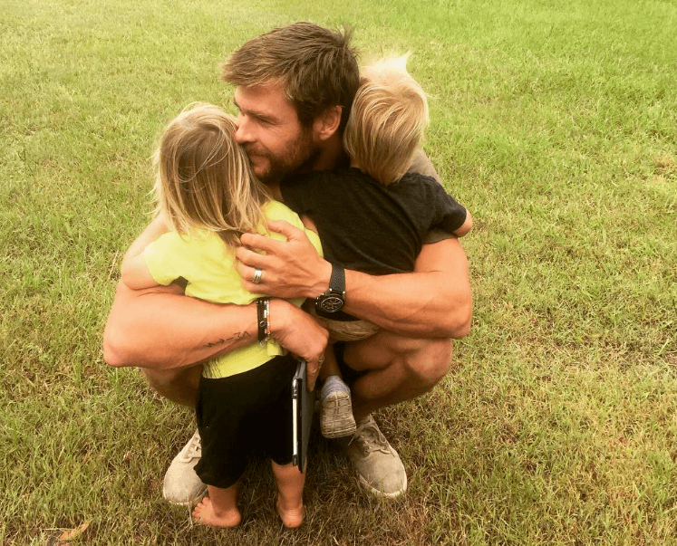 Chris Hemsworth hugging his twin sons in the grass