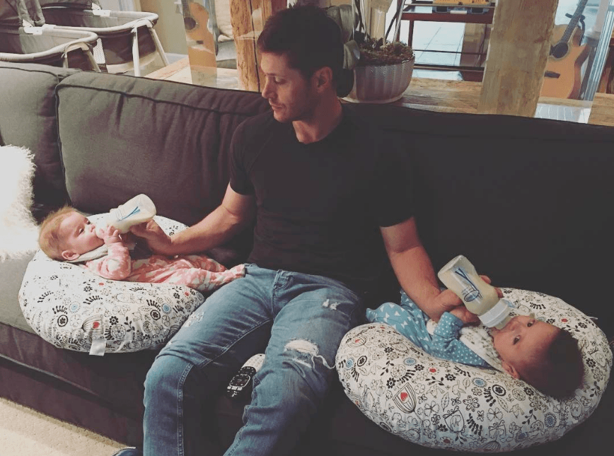 Jensen Ackles sitting on a couch feeding both of his infant twins with bottles