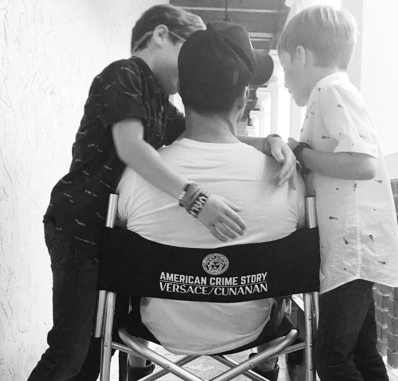Ricky Martin sitting in a folding chair facing away with his sons hugging him