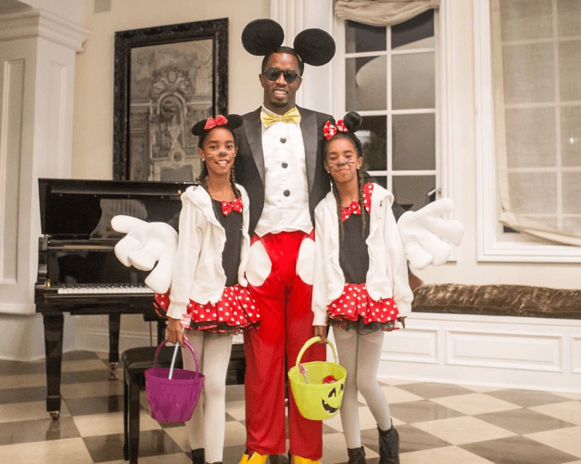 Diddy dressed as Mickey Mouse posing with his twin daughters dressed as Minnie
