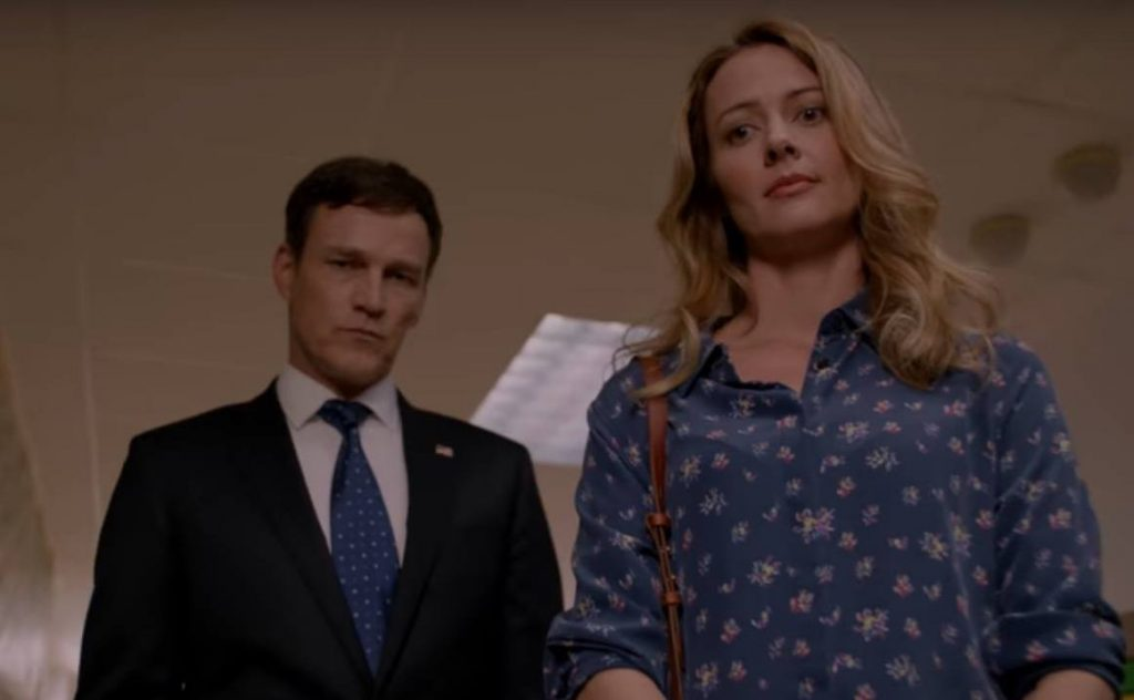 Stephen Moyer in a suit, and Amy Acker in a blue dress, both standing in a school hallway looking down