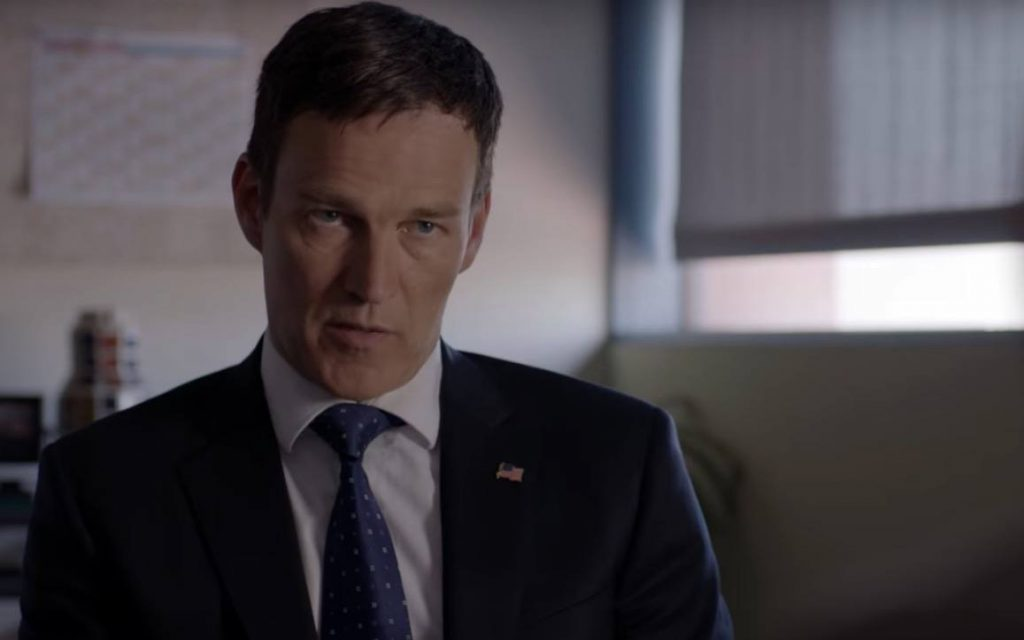 Stephen Moyer wearing a suit with an American flag pinned to the collar, sitting in an office