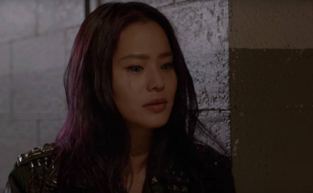 Jamie Chung with purple hair and eyes, leaning against a wall and looking downward