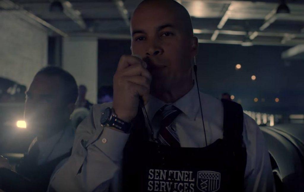 Coby Bell wearing a bulletproof vest, speaking into a walkie-talkie