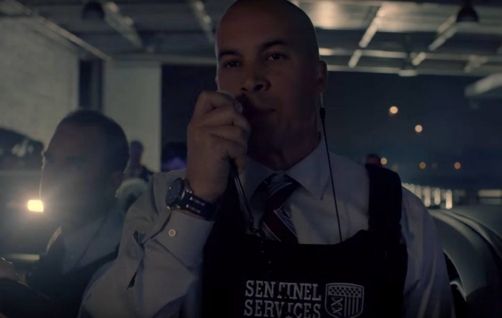 Coby Bell wearing a bulletproof vest, speaking into a walkie-talkie