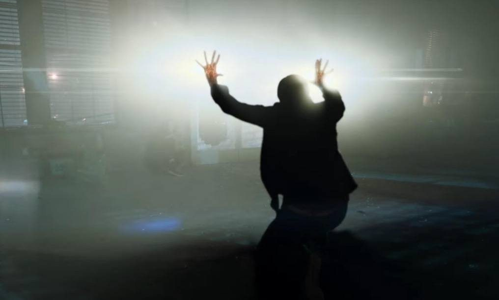 A man with light coming from both hands hold both up with his back turned to the camera