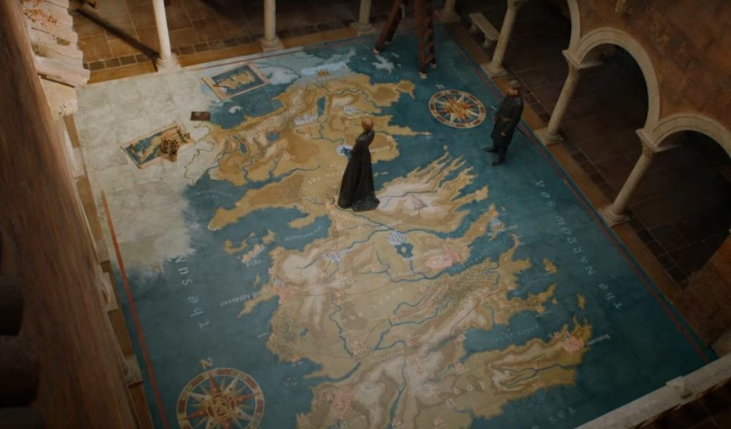 Cersei stands on top of a floor with a map of Westeros, with Jaime directly to her right