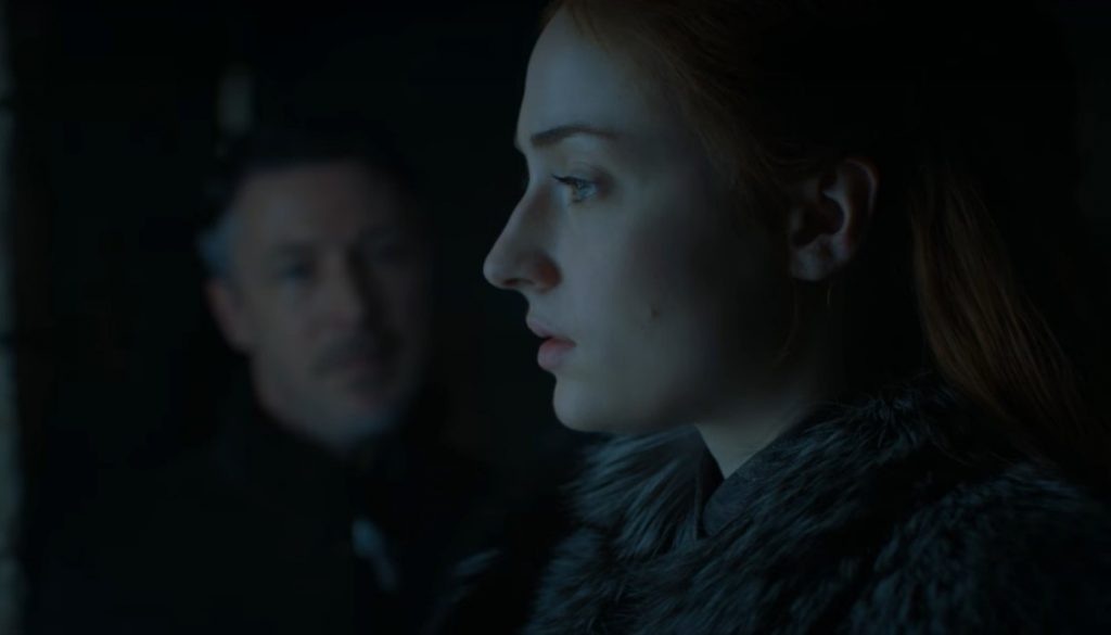 Sansa in the foreground, looking pensively to the left of the frame, with Littlefinger advising her from the shadows in the background