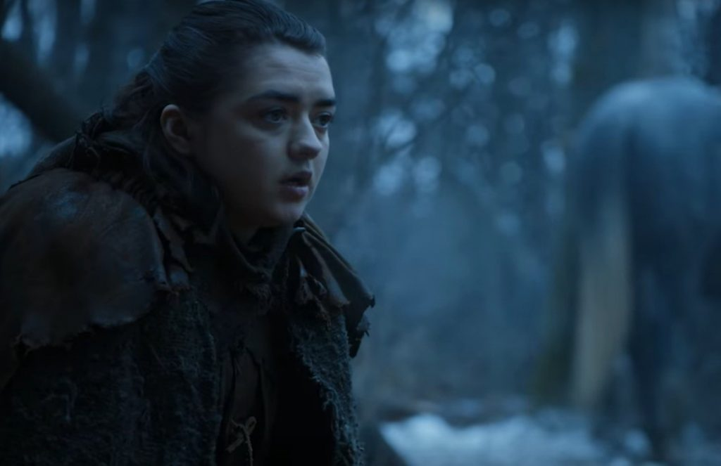 Arya sits at a campfire, looking to the right of the frame in the snow