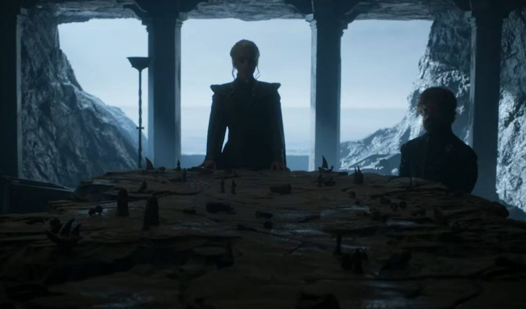 Daenerys stands over a table shaped like Westeros, with Tyrion off to her left