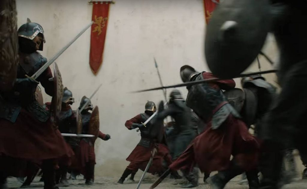 Two armies clash, with red banners bearing a lion hanging from the back wall