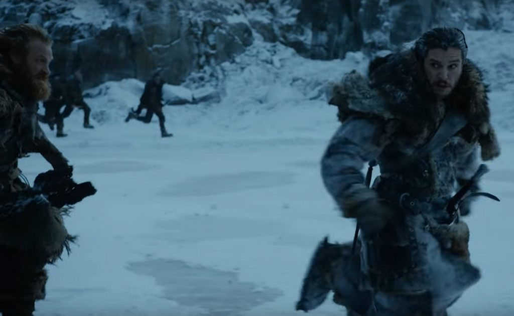 Jon Snow wearing furs, looking startled, and running to the right of the frame in the snow